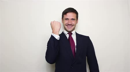 çok güzel : Handsome young businessman actively expresses joy, makes a gesture with his hand and says yes. Stok Video