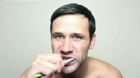 getting ready : Young handsome guy brushing his teeth while looking into the camera.