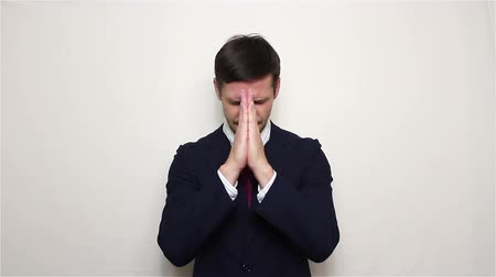 acreditar : Young handsome businessman praying speaks please, asking God for help in business