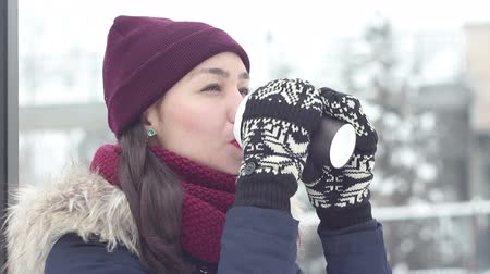 мороз : Beautiful young girl in a romantic mood with pleasure drinks coffee through a straw in a winter park. Стоковые видеозаписи