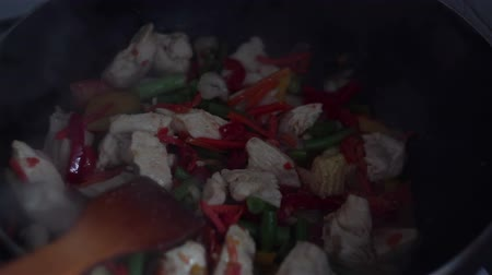 vegetable wok : Chef cooks chicken with vegetables in a wok pan.