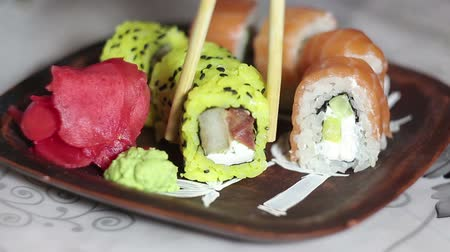houten bord : Hand with chopsticks takes sushi from the plate. Stockvideo