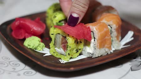 roll up : Female hand takes pickled ginger, puts it on a sushi roll and picks it up from the plate.