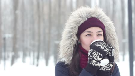 мороз : Beautiful young girl enjoy winter view and drinks coffee in the snowy park.
