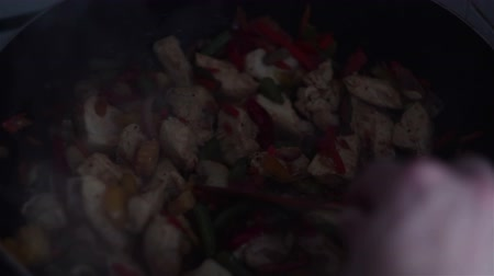kırmızı biber : Chef mixes a chicken and vegetable dish in a wok pan with a wooden spatula Stok Video