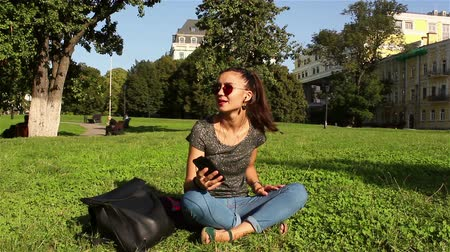 jovial : Beautiful young girl sits on the grass in the park and listens to her favorite tune on the phone.