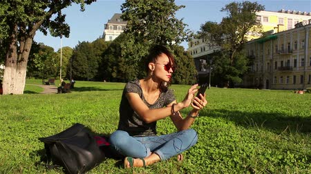 jovial : Beautiful smiling young girl, sitting on the grass in the park, turns on her favorite melody in the phone.