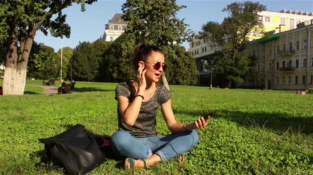 jovial : Beautiful young girl wearing sunglasses, sitting on the grass in the park, turning on her favorite melody in the phone.