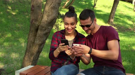 фотографий : Couple in love show photos on their smartphones with each other, sitting on a park bench. Стоковые видеозаписи