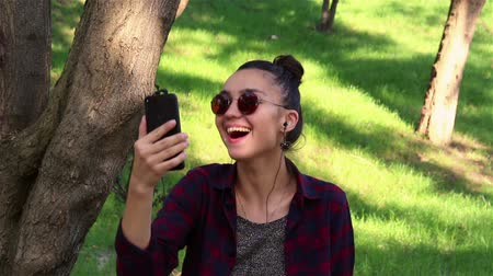 клетчатый : Beautiful girl in sunglasses, actively laughing, looking through the news on social networks, sitting on a park bench.