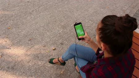 alpha cell : Young beautiful girl listening to music on her smartphone, sitting on a bench in the park. Stock Footage