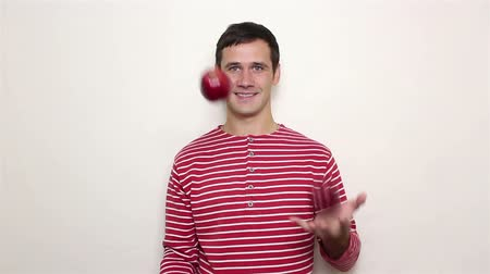 disguise : Young handsome guy in a striped sweater juggles with three red apples.