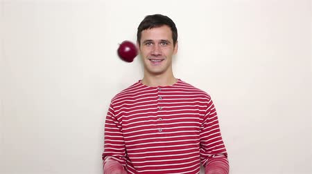 disfarçar : Young handsome guy in a striped sweater smiles broadly and juggles with three red apples. Vídeos