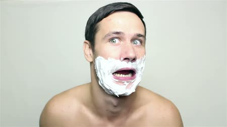 shaving foam : Young handsome guy applies shaving foam and smiles.