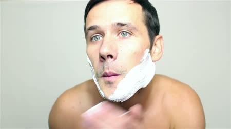 бритье : Young handsome guy applies shaving foam about to shave.