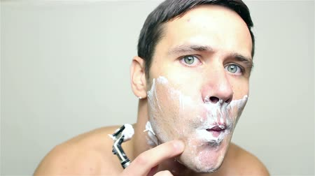 barbear : Young handsome guy shaves his face with a razor.