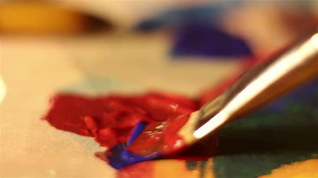 squeeze : Artist lowers the brush in red paint and mixes it on the palette. Stock Footage