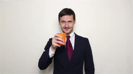 parceiro : Young handsome businessman drinks alcohol from an orange cup. Vídeos