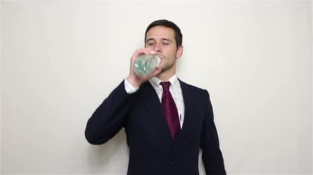 sede : Young handsome businessman is smiling and drinking water from a plastic bottle. Vídeos