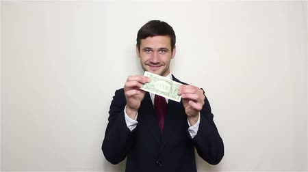 получать : Young handsome businessman pulls one dollar out of his pocket and shows it.