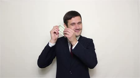 получать : Young handsome businessman is listening to the rustle of a dollar.