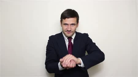 связать : Young handsome businessman squeeze a dollar in his hands and throws it behind his back.