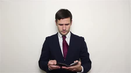 связать : Young handsome businessman pulls out a dollar from his wallet and stretches it to the camera.