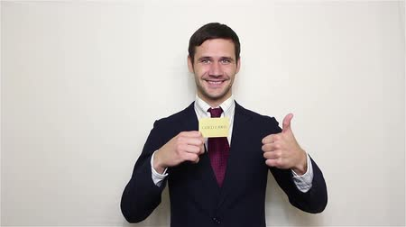 кошелек : Young handsome businessman shows his golden credit card, smiles and shows thumb up.