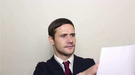 burocracia : A young handsome businessman picks up a sheet of paper with a contract and reads it carefully.