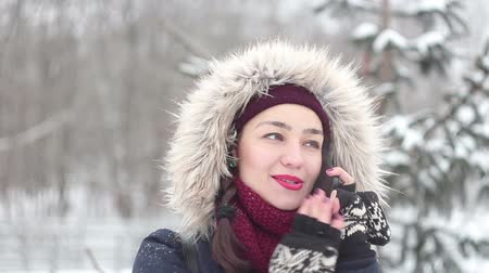 snow caps : Young beautiful girl actively talking on her smartphone while standing in a winter park. Stock Footage