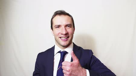 szám : Young handsome businessman smiling and showing thumb up . Stock mozgókép