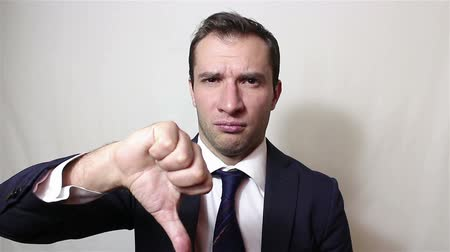 proibir : Young handsome businessman shows thumb down, expressing his displeasure.