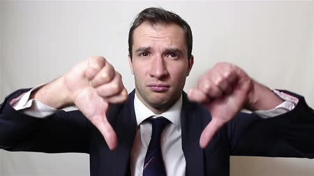 снижение : Young handsome businessman shows thumb down with two hands, expressing his displeasure.