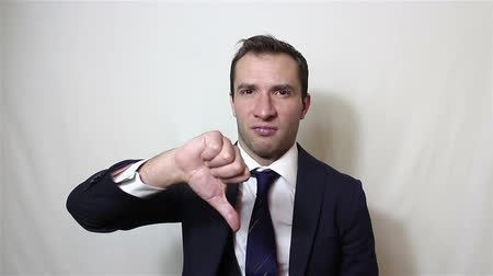 снижение : Young handsome businessman shows thumb down, expressing his displeasure.