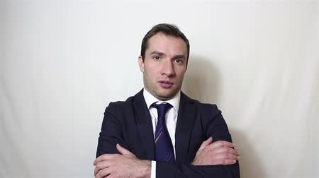 hűség : Young handsome businessman folds his arms and looks sarcastically at the camera.
