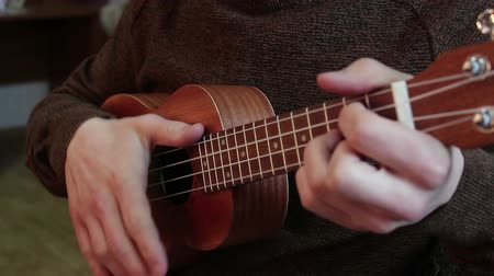 kytarista : Hands of a young guy playing the ukulele. Dostupné videozáznamy