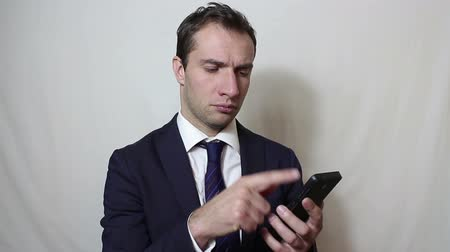 bolso : Young handsome businessman pulls out his smartphone from his pocket and looks through the news feed. Stock Footage
