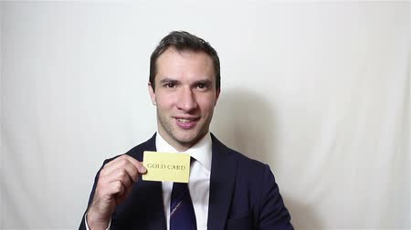 дебет : Young handsome businessman shows his golden credit card.