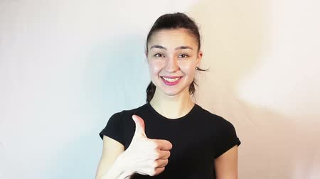 female hands : A beautiful young girl in a black t-shirt is smiling and showing thumb up looking at the camera.