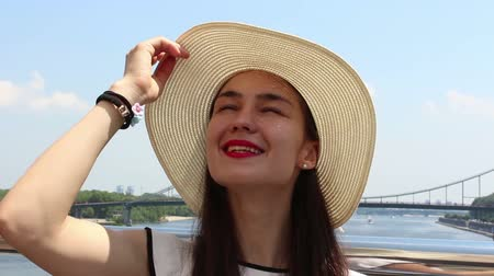 elevação : Close up portrait of a beautiful young girl in a white hat. Young Attractive Girl in a white hat, raises her gaze to the sky and squints from the sun.