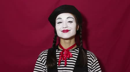 comediante : Beautiful girl mime smiles and makes a gesture of a beating heart with her hands looking at the camera. Beautiful girl in the image of a mime folds a heart from her hands looking at the camera.
