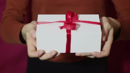 Beautiful girl holds out a gift in a white box, with a red ribbon. Beautiful girl hands hold a New Years gift, in a white box with a red ribbon. Gift for the holiday. Stock mozgókép
