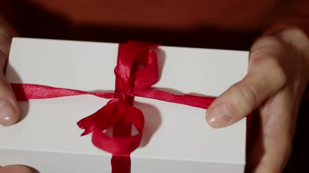 Beautiful girl holds out a gift in a white box ,with a red ribbon. Beautiful girl hands hold a New Years gift, in a white box with a red ribbon. Gift for the holiday. 動画素材