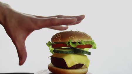 bun : Male hand takes a big burger from a plate. Big juicy burger with beef cutlet, fresh vegetables and cream cheese. Young mans hand takes a hamburger from a plate. Stock Footage