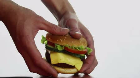 apetitoso : Mens hands take a large burger from a plate. Big juicy burger with beef cutlet, fresh vegetables and cream cheese. Burger close-up on a white background.