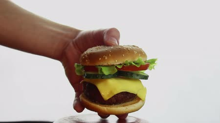 Male hand takes a big burger from a plate. Big juicy burger with beef cutlet, fresh vegetables and cream cheese. Young mans hand takes a hamburger from a plate. 動画素材