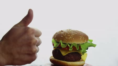 бекон : Male hand shows thumb up on fresh juicy burger. Large juicy burger with beef cutlet, fresh vegetables and melted cheese. Fast food, high-calorie food.
