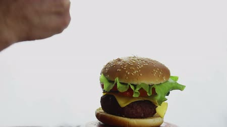 fast food : Male hand shows thumb up on fresh juicy burger. Large juicy burger with beef cutlet, fresh vegetables and melted cheese. Fast food, high-calorie food.