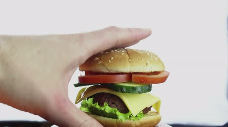 engorda : Female hand takes a big burger from a plate. Big juicy burger with beef cutlet, fresh vegetables and cream cheese. Hand of a young girl takes a hamburger from a plate.