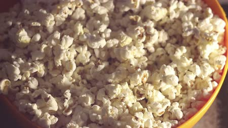 жадный : Fresh hot popcorn drops in a bowl.Fresh crispy popcorn drops in a bucket.